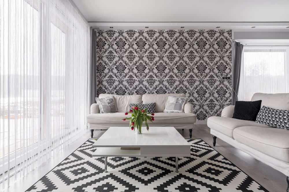 This elegant living room has black and white patterns dominating the wallpaper and the area rug underneath the white modern coffee table. The two comfortable sofas follow this theme with white cushions and black wooden legs that contrast the white flooring.
