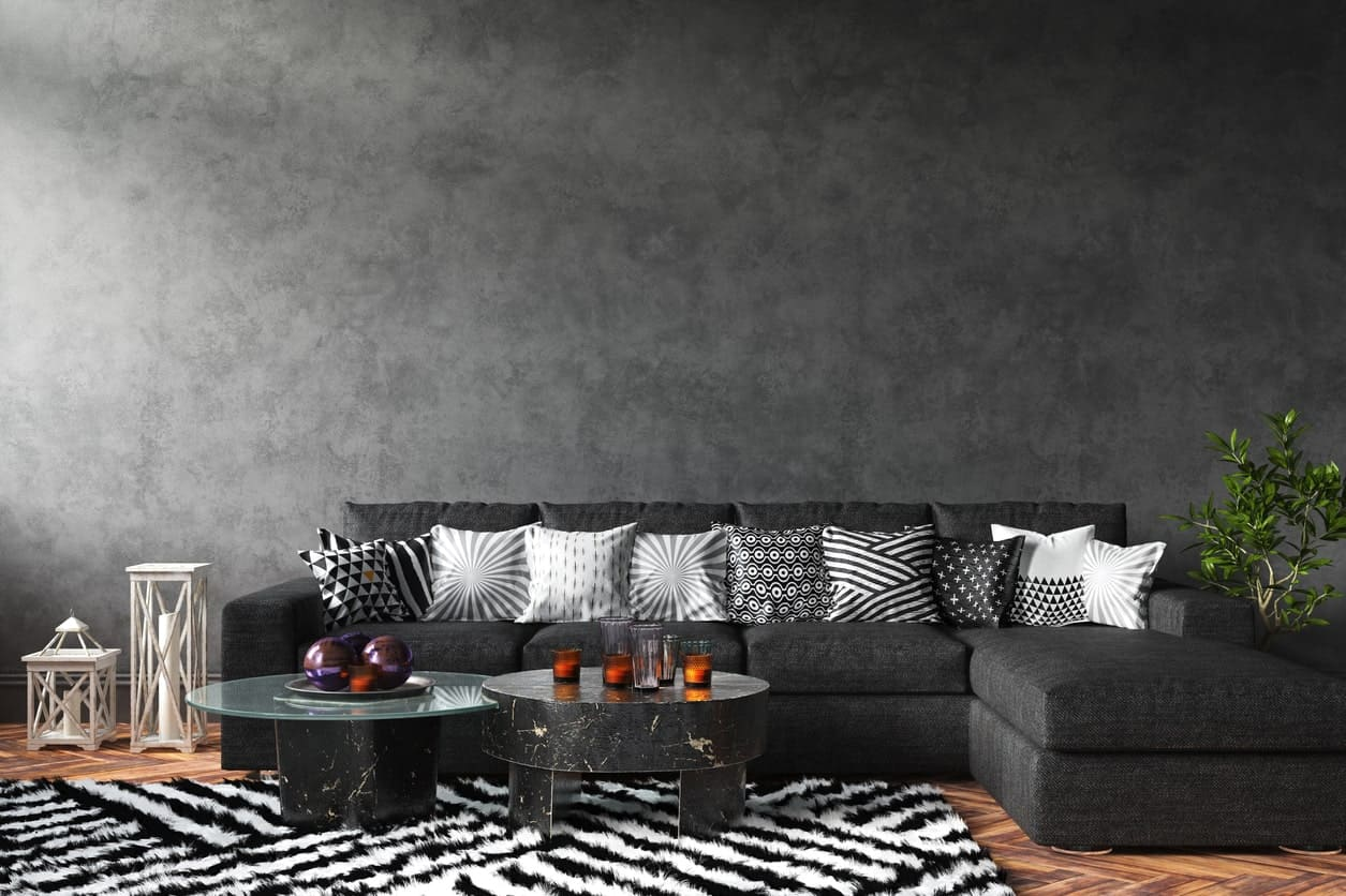 This living room offers a black L-shape sofa along with stylish black center tables set on a white and black rug covering the hardwood flooring.