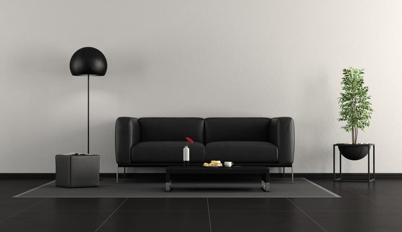 Minimalist black living room featuring black tiles flooring, a gray area rug and a black couch matching the black center table.