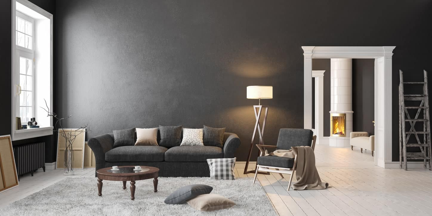 Large living room featuring black walls matching the black sofa set on the hardwood flooring topped by a gray rug.