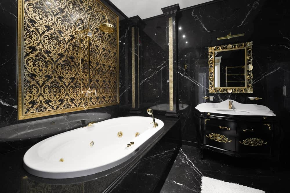 The white bathtub perfectly contrasts the black marble housing it that extends to the walls. The showerhead appears invisible against the intricate gold patterns of the wall above the bathtub. This gold and black theme is also applied to the vanity area.