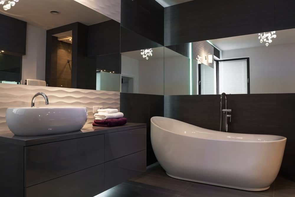 The walls of this bathroom have several sections of different materials. One part has a dark gray laminate that contrasts the white textured backsplash. Lastly, a strip of the walls is covered by frameless mirrors that work well with the white bathtub.