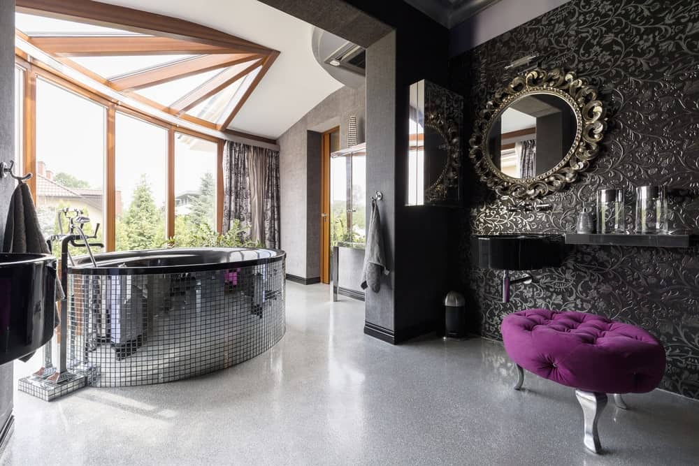 This is a chic black bathroom with elements of purple mixed in with the black and gray palette of the room. The bathtub that is covered with mirror tiles like a disco ball is a perfect fit for its spot by the massive windows. This makes the natural light reflect on the rest of the room.