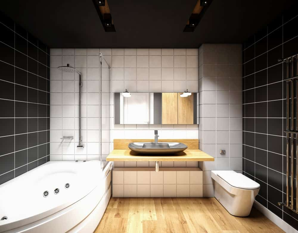 The two walls flanking the room has black tile that extends to the black ceiling. This is paired with white grout to emphasize the lines. The contrast comes from the brightness of the vanity area and the bathtub paired with hardwood flooring.