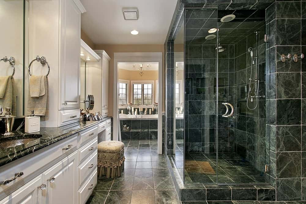 The shower area of this bathroom has black marble walls and flooring that extend to the rest of the bathroom. This black marble flooring is matched with the countertop of the vanity area that has white built-in cabinets and drawers.