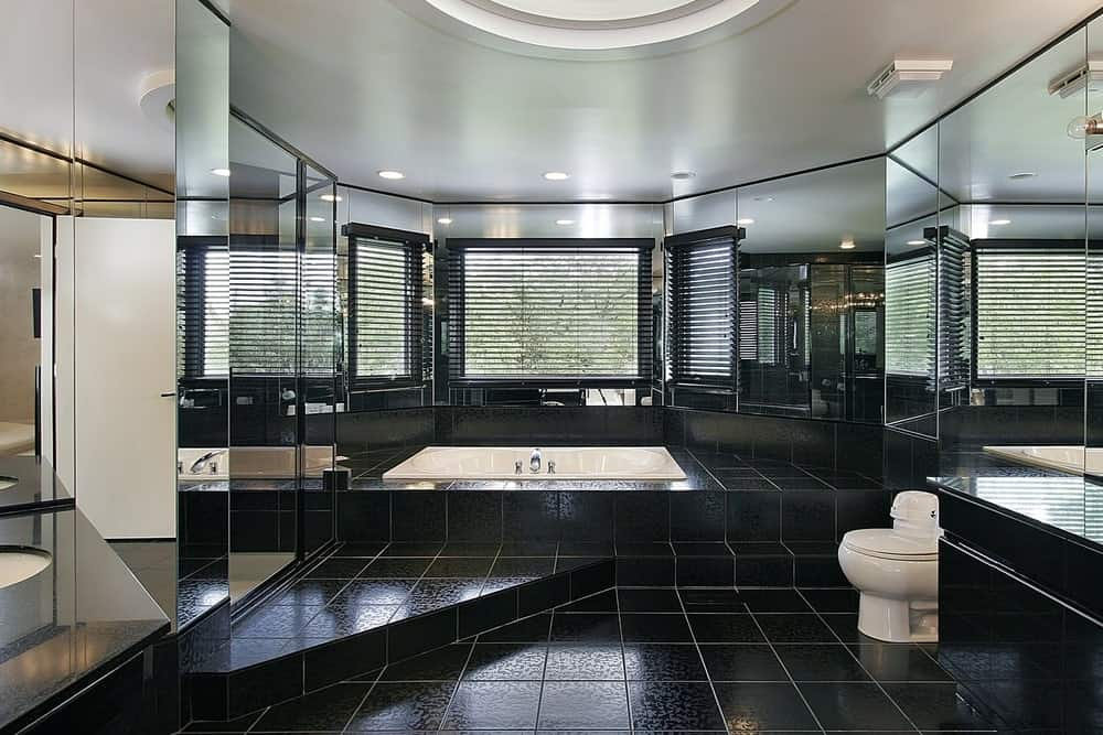 This black bathroom has layers of sleek elegance. First is the white ceiling that follows the round lay of the room. Second is the walls that are totally dominated by mirrors and a bright window looking over the bathtub. The third is the sleek black-tiled flooring that totally elevates the aesthetic to whole new heights.