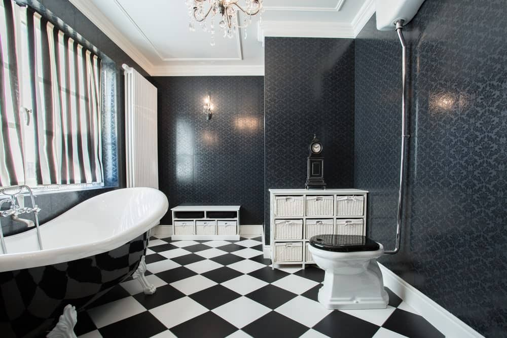 The bathtub has a black and white design that matches the toilet and the checkered flooring of this black primary bathroom. The walls are a whole different story of elegance with its subtle patterns within the black background which is augmented by a white tray ceiling.