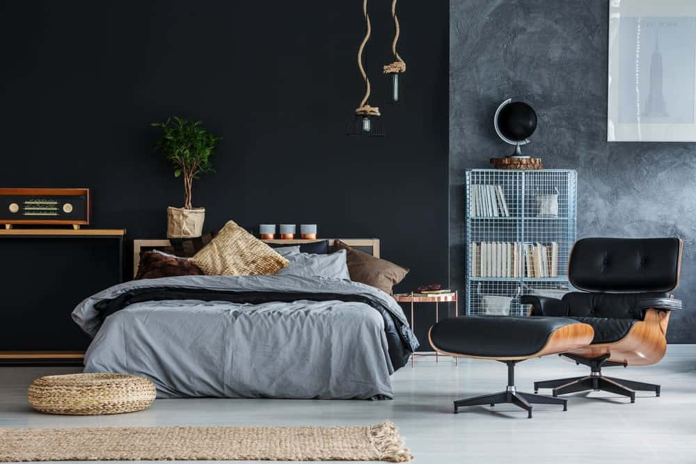 This primary bedroom features black and gray walls along with a modish and handsome-looking chair with a footrest.