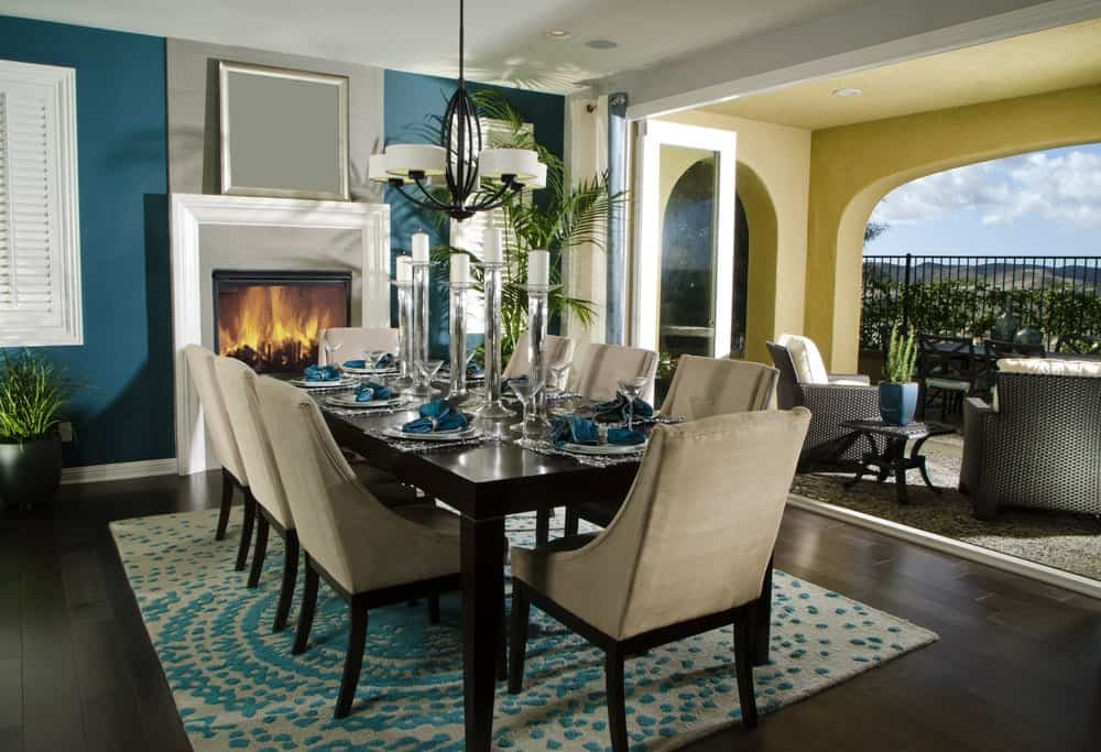 An elegant dining table and chairs setup on top of a blue rug covering the hardwood flooring. The space features a fireplace and a modish chandelier.