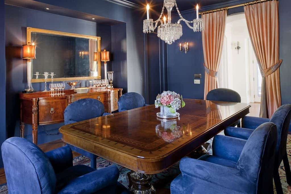 A dining room featuring blue walls, matching the blue seats. The chandelier looks very fancy. The orange window curtains look just perfect together with the room's style.