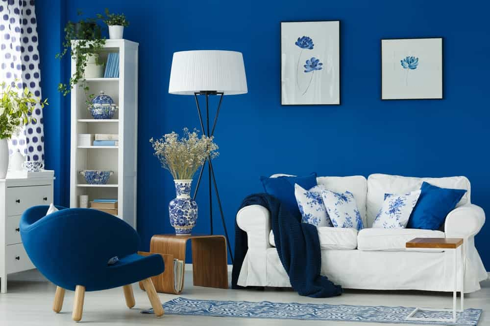Blue living room featuring a matching blue chair and throw pillows on the white couch.