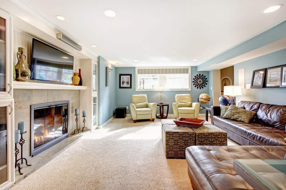 Large living room featuring carpet flooring and sky blue walls. The room offers a brown leather sofa set and a fireplace along with a TV on top of it.