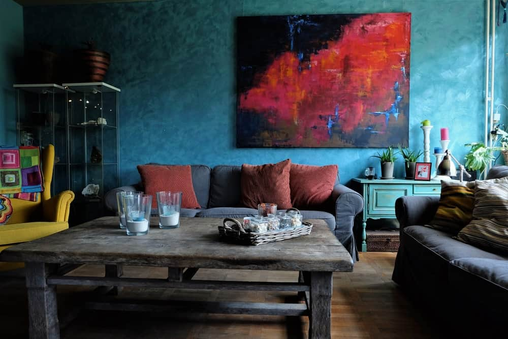 This living room boasts blue walls with an artistic abstract wall decor. The gray couches look handsome together with the rustic center table.