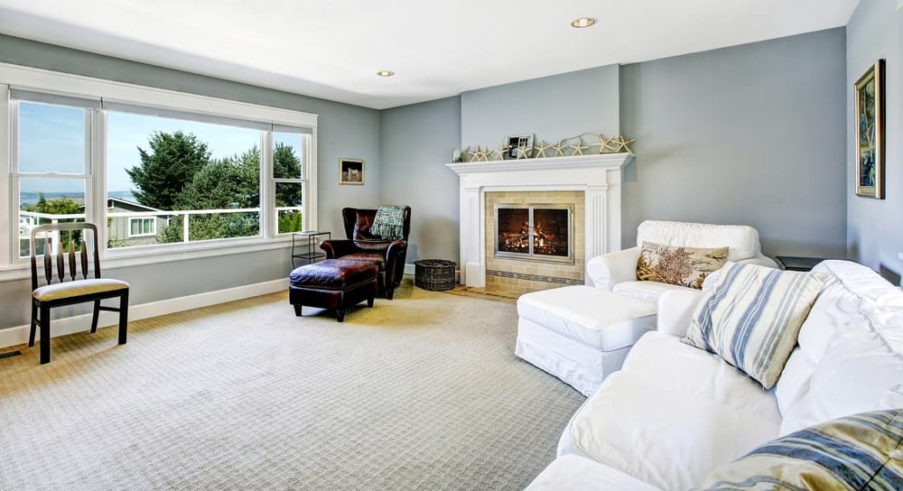 Spacious living room featuring blueish gray walls and carpet floors, along with a white sofa set and a white chair.