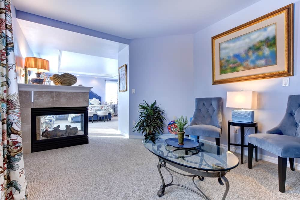 A primary suite with its own living room. It has a blue theme featuring blue walls and a pair of matching chairs. There's a classy glass top table and a fireplace.