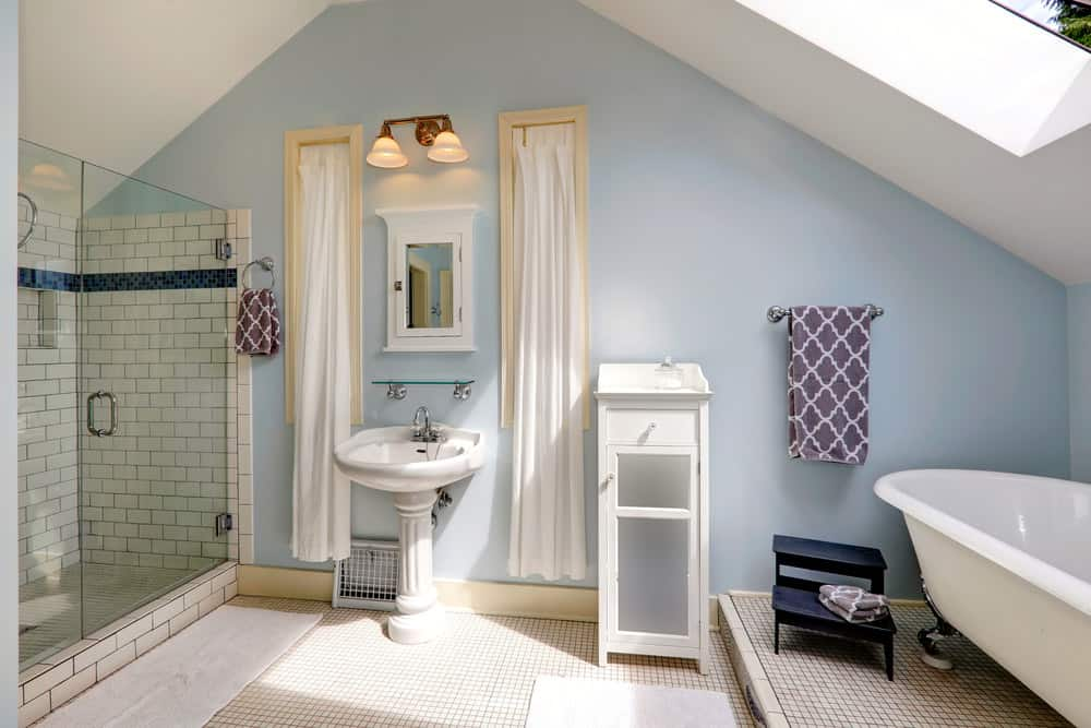 Master bathroom featuring light blue walls. It also offers a pedestal sink, a walk-in shower and freestanding tub set under the skylight.
