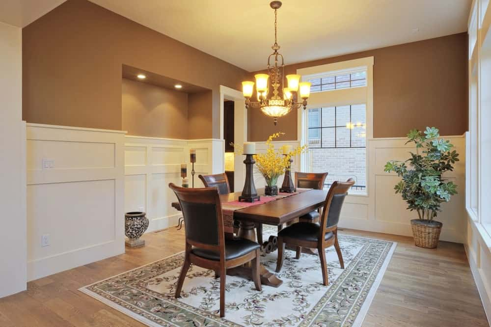 This formal dining room has chocolate brown walls with white wooden finishing on the lower half that blends with the white frames of the tall window. This brilliant window illuminates the dark brown wooden dining table and matching dining chairs that have black leather cushions.