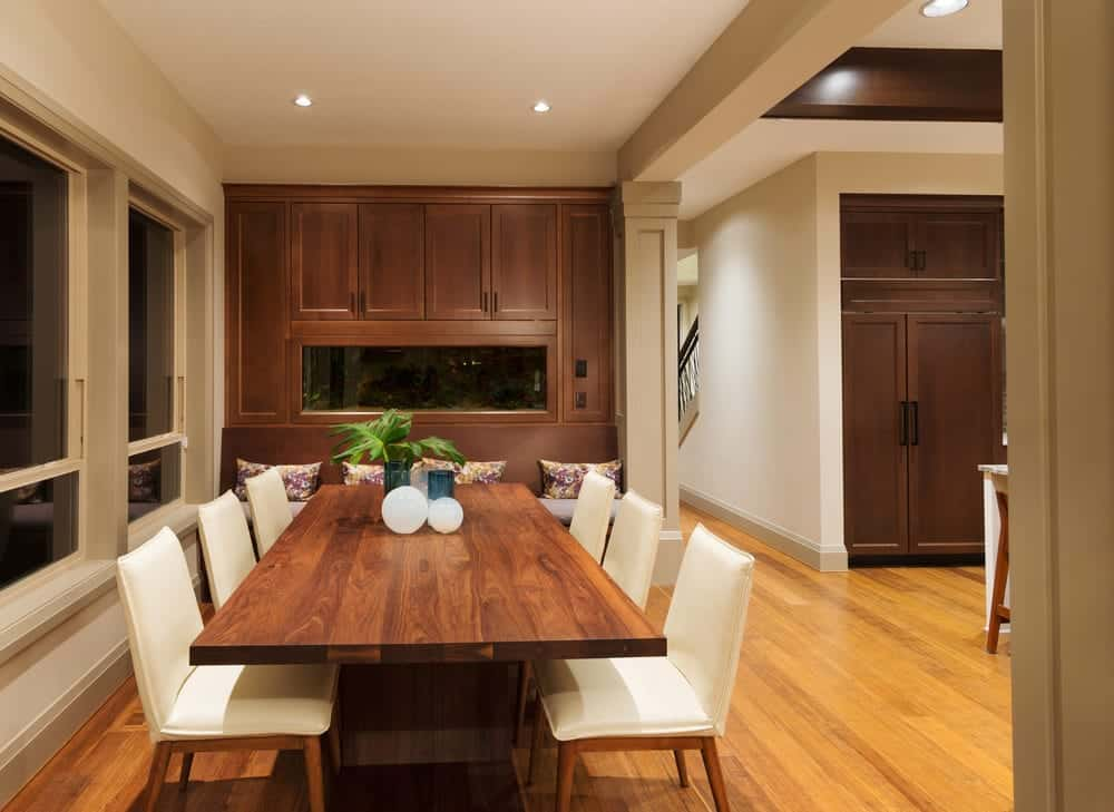 A simplistic dining area featuring a wooden dining table with white chairs along with a bench seating on the side.