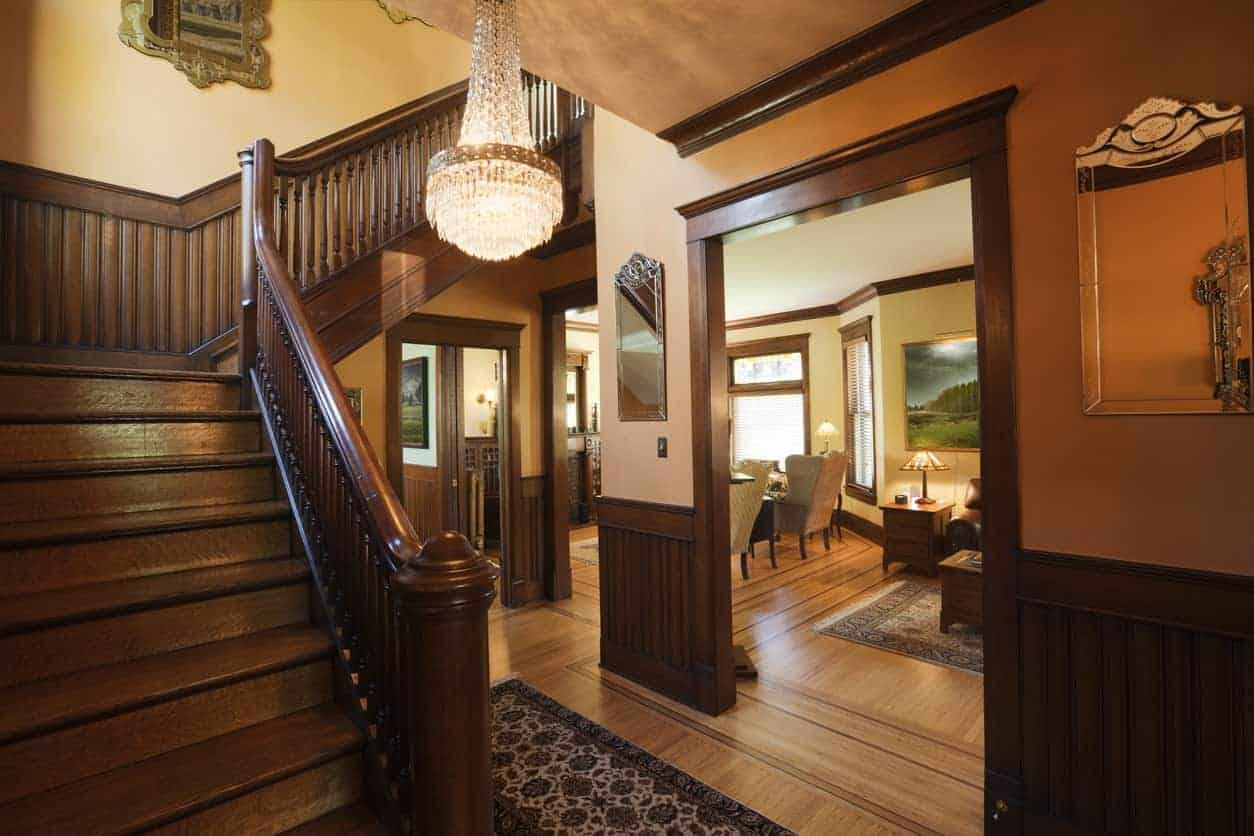 A closeup look at this foyer with wooden staircase and stylish mirrors mounted above the beadboard walls. It is illuminated by a fancy crystal chandelier that hung from the concrete ceiling.