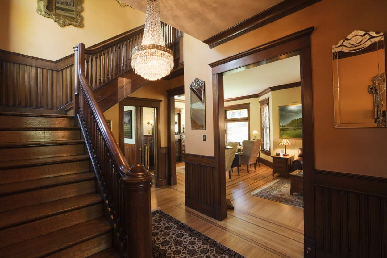 This is an elegant brown foyer dominated by the dark wooden finishings of the walls that complement the wooden flooring that is topped with a dark patterned area rug. There is an elegant small crystal chandelier hanging from the light brown ceiling.