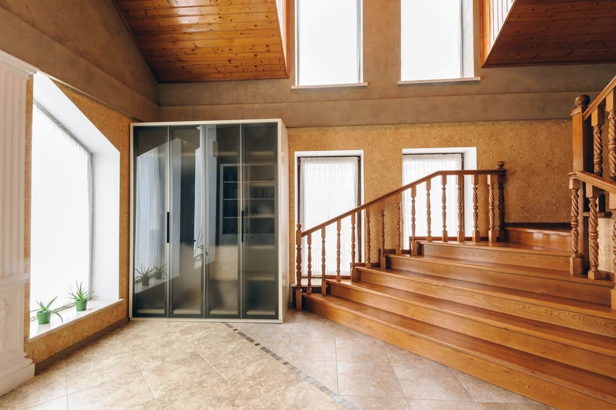 This is a wide and airy grand foyer that has a high ceiling and brown walls dominated by an abundance of tall windows that bring in natural light over the marble flooring. There is a mudroom by the wooden stairs that has shelves covered with frosted glass.