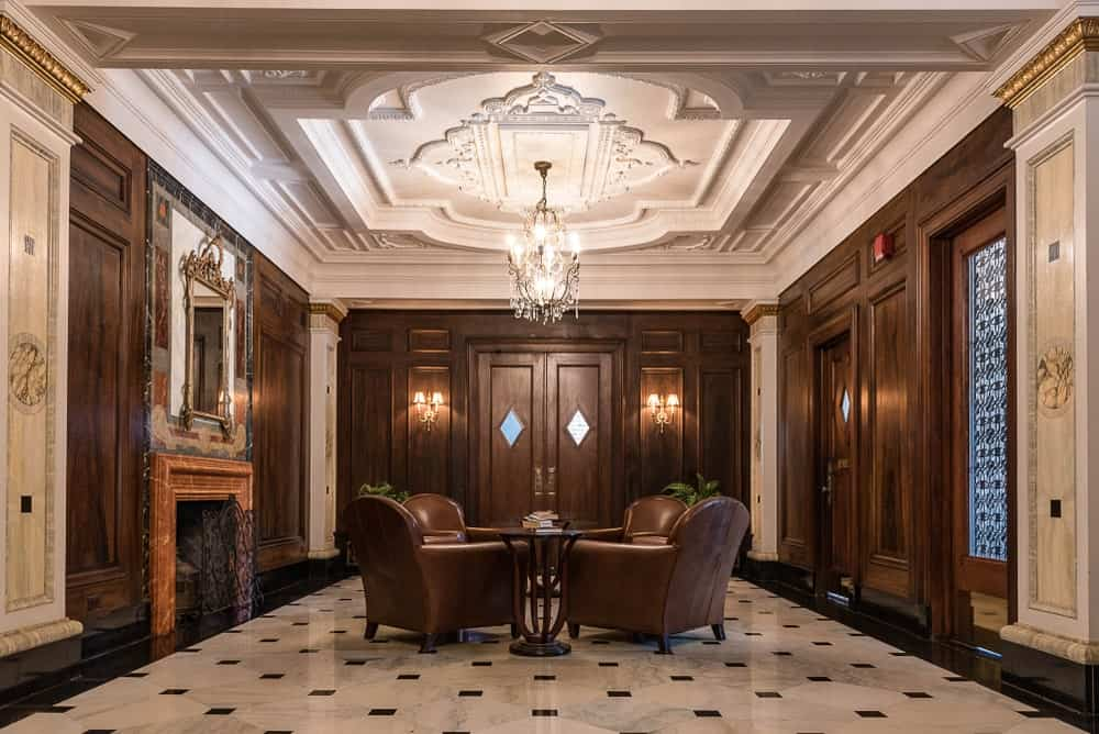 This grand foyer exudes luxury and elegance with its sleek black and white marble flooring paired with a set of brown leather cushioned armchairs and a fireplace on the brown wooden wall that has a wall-mounted mirror at the top for a degree of warmth.