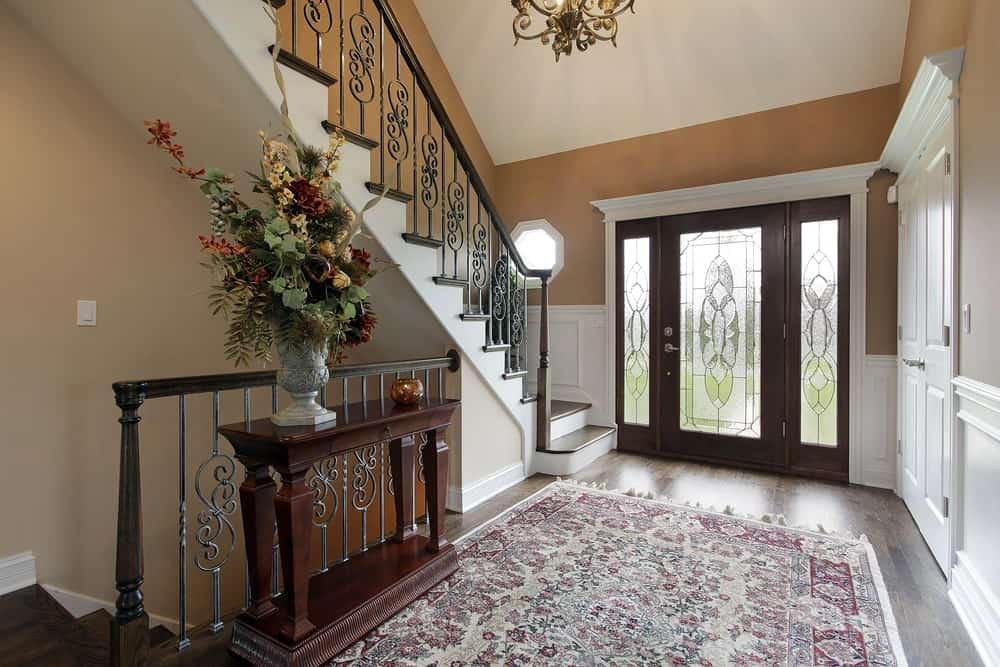 The wooden main door of this foyer is surrounded by a white finishing that stands out against the brown walls and hardwood flooring. This flooring is topped with a floral patterned area rug that is brightened up by the natural light coming in from the frosted glass fixed into the main door and its sidelights.