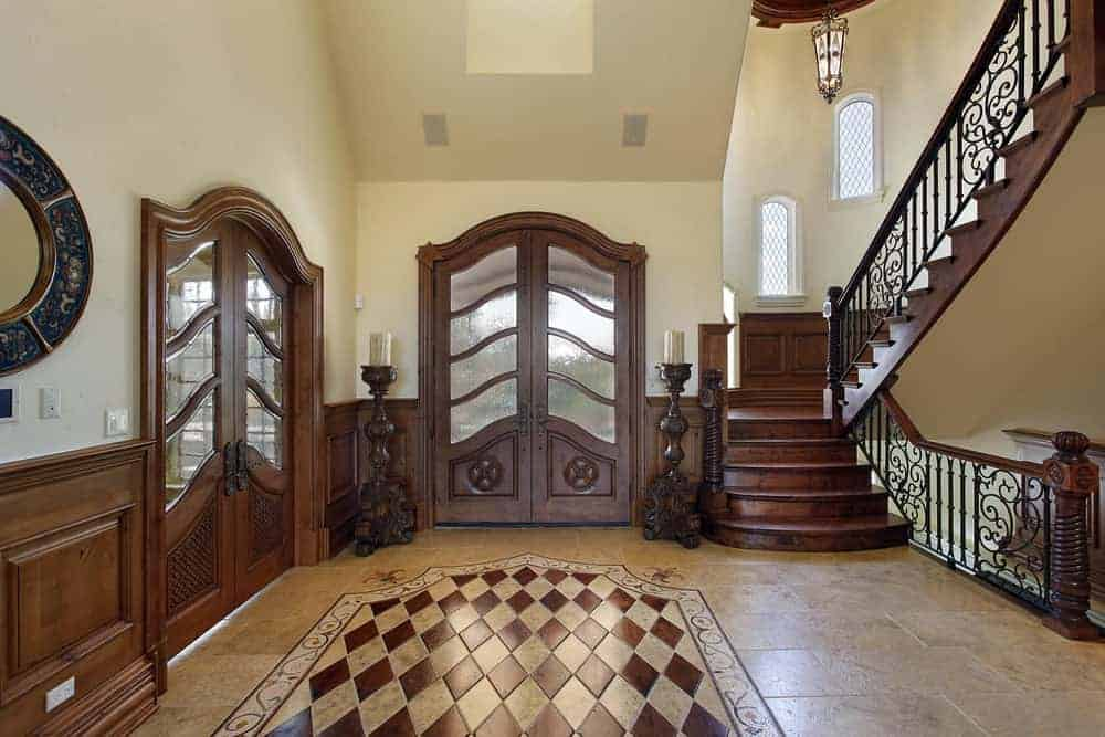 This foyer features arched french doors with carved wood candles on its sides. It includes a wooden staircase illuminated by a pendant light.