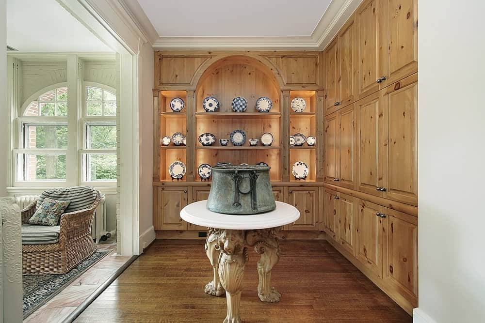This is a simple foyer that has a large wooden structure dominating two adjacent walls. It has built-in cabinets in three tiers all the way to the white ceiling. It also has open shelves that are used to display porcelain plates. In the middle of the hardwood flooring is a circular table with lion-head designs on its legs.