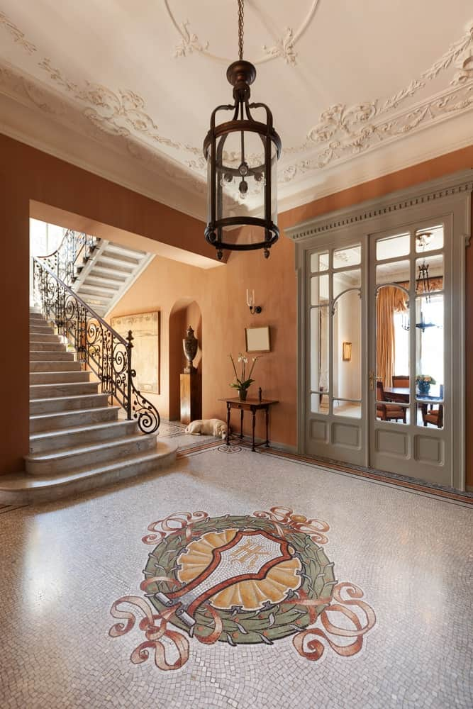 The earthy brown walls of this wide foyer is a nice background for the intricate details of the mosaic floor with an emblem in the middle and the white tray ceiling that is framed with intricate elegant details.