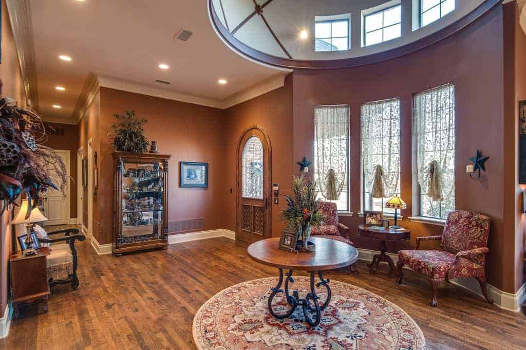 Brown foyer with a display cabinet and wooden center table that sits on a round rug. It includes a seating area by the window featuring red floral armchairs and a round table in between.