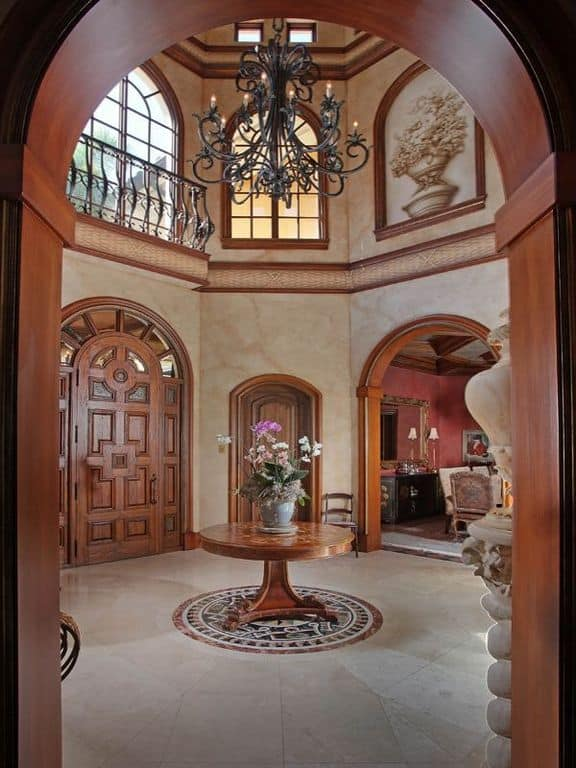 An arched wooden door opens to this foyer surrounded with open archways. There's a round center table in the middle illuminated by a vintage chandelier.