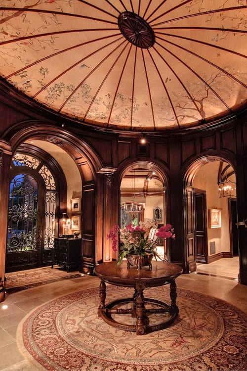 Gorgeous foyer boasts a lovely dome ceiling and tiled flooring topped by a round rug. It has a wooden console table surrounded with open archways and an ornate front door.