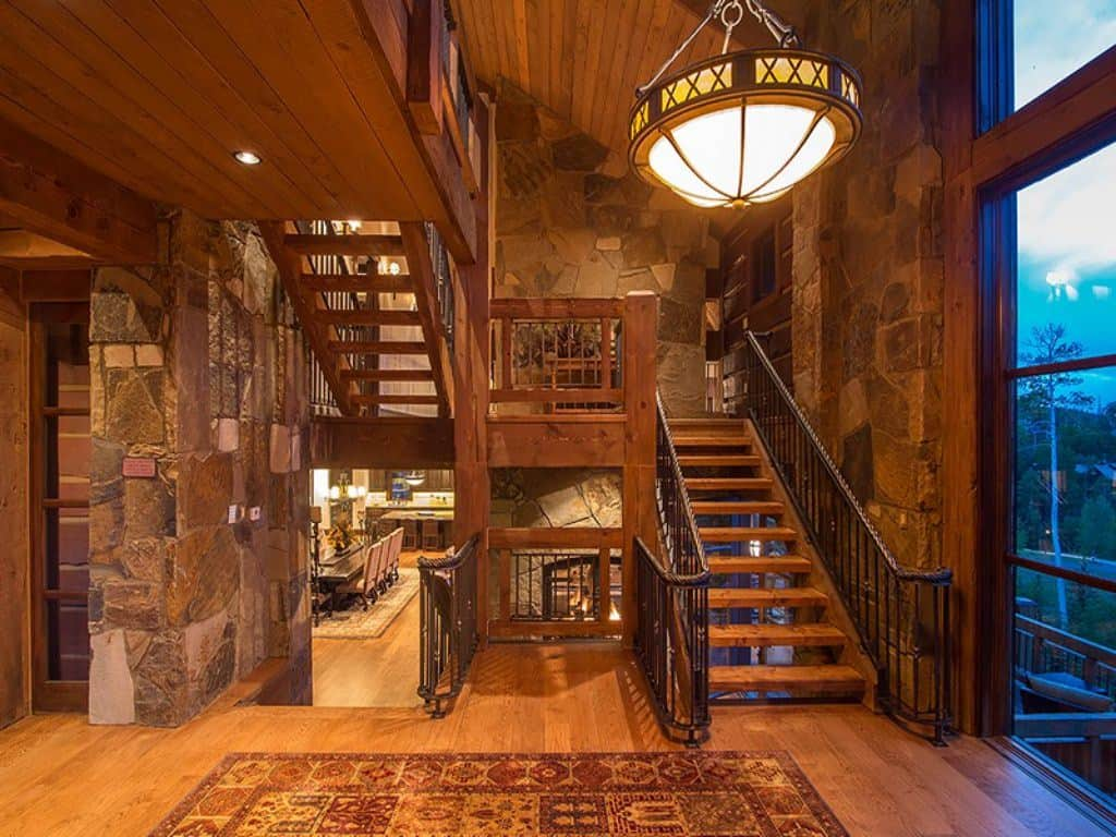 Warm foyer features stone walls and vaulted wood beam ceiling with a hanging pendant light. It has a wooden staircase that matches with the hardwood flooring.