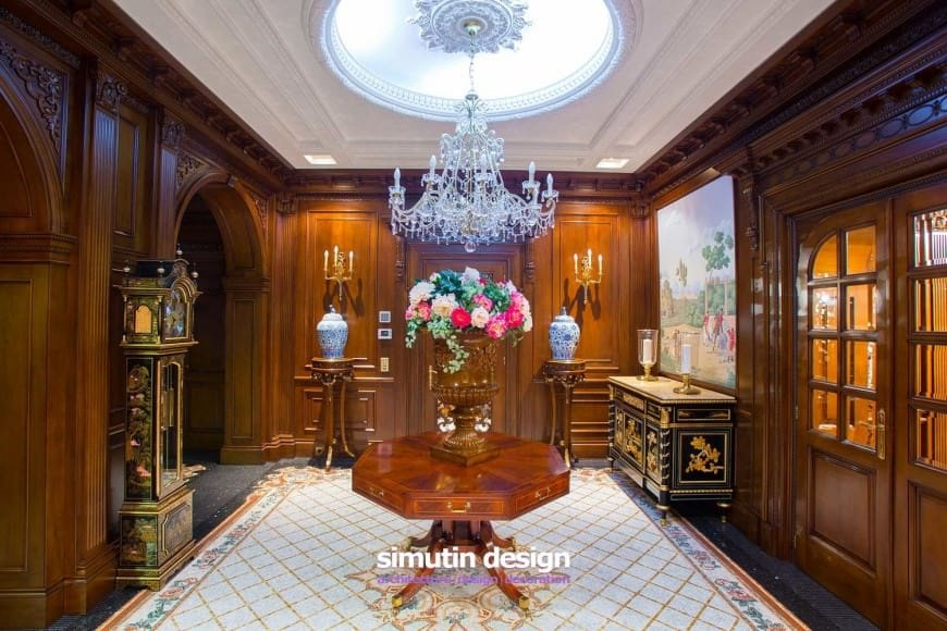 Fabulous foyer offers an octagonal center table and a stylish black console table situated beneath the lovely wall art. It includes a pair of pedestals topped with ceramic vases and lighted by candle sconces.