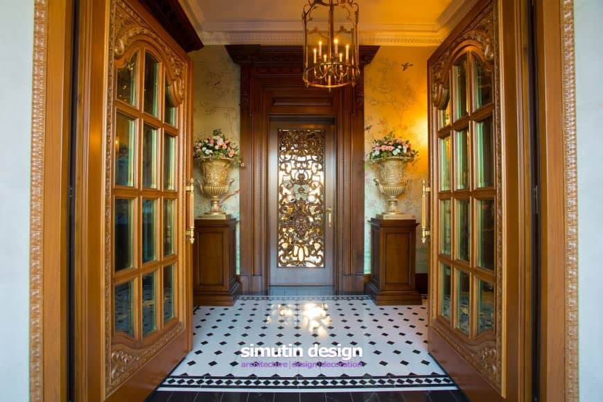 A wooden french door opens to this elegant foyer with a stylish door in between wooden pedestals that are topped with gold flower vases.