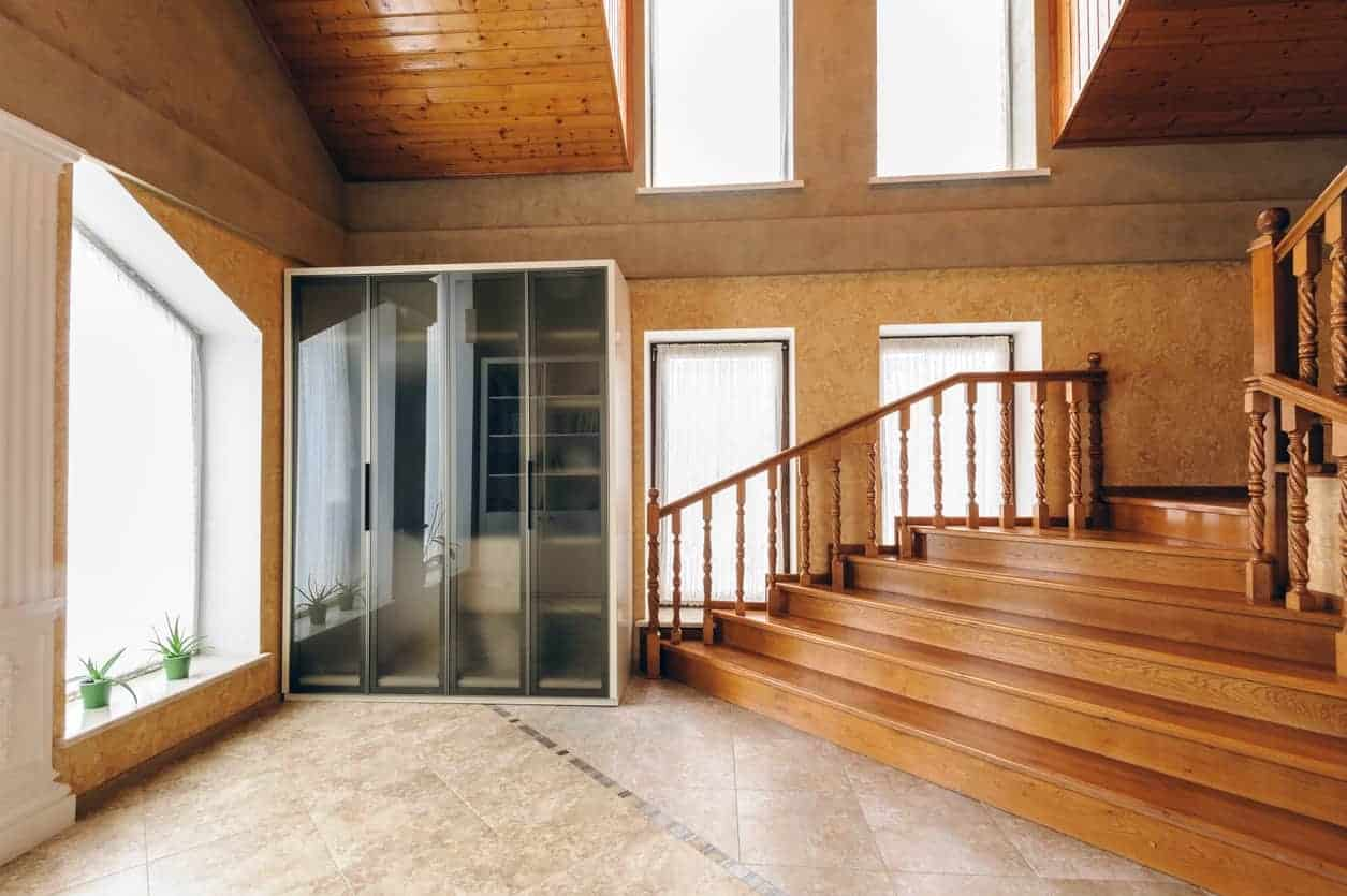 Brown foyer showcases glass windows and limestone flooring. It includes a glass front storage cabinet next to the wooden staircase.