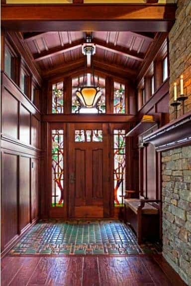 An all wood foyer boasting paneled walls and cathedral ceiling with a hanging pendant light. It has a rustic front door surrounded with lovely stained glass.