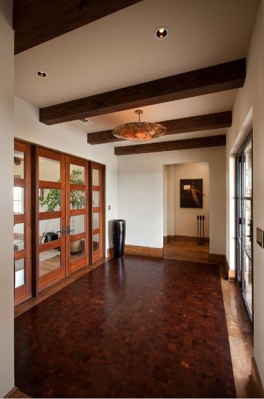Spacious foyer features a black vase in the corner and a wall art at the far end mounted on the white wall. It is illuminated by a pendant light that hung from the wood beam ceiling.