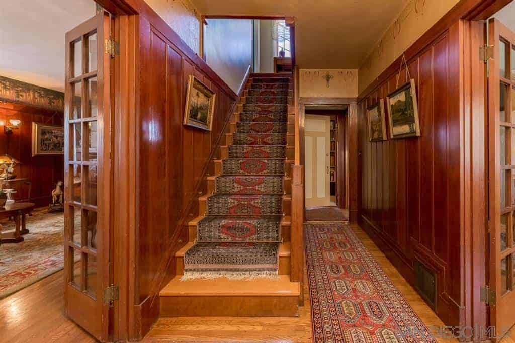 Craftsman style foyer decorated with framed wall arts mounted on the beadboard walls. It has a hardwood flooring and wooden staircase both topped with vintage rugs.