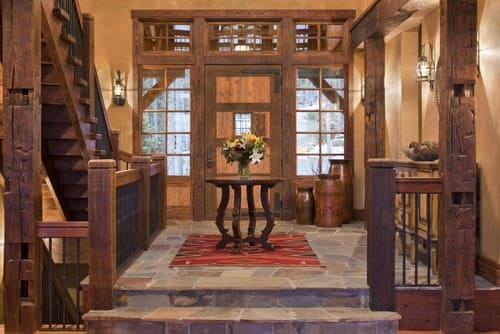 A round wooden table is the focal point in this rustic foyer framed with tree trunk columns. It has a wooden staircase and stone flooring topped with a red rug.