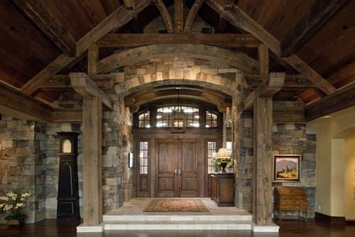 Rustic foyer showcases a wooden double door and cathedral ceiling with exposed wood beams. It includes a console table paired with a mirror that's mounted on the stone brick wall.