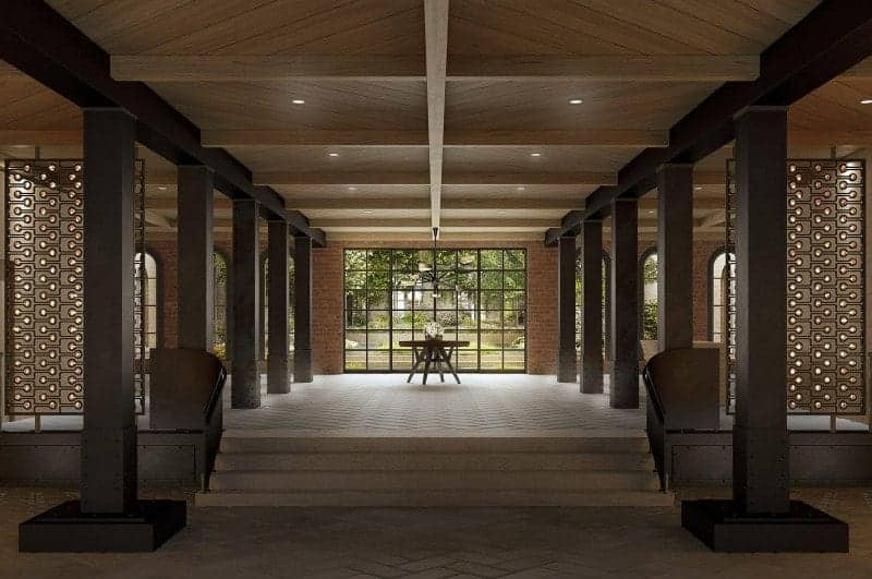 An expansive foyer with a wooden center table by the framed full height glazing lined with dark wood columns.