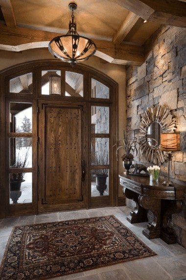 Spanish foyer decorated with a sunburst mirror that's mounted on the stone wall and above a dark wood console table. It has a rustic front door surrounded with glass panels along with limestone flooring topped by a vintage rug.
