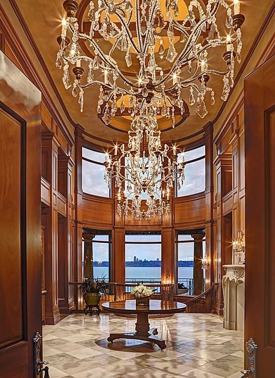 Deluxe foyer illuminated by a pair of grand crystal chandelier that hung over the glossy center table. It has diamond pattern flooring and glass paneled windows overlooking a stunning outdoor view.