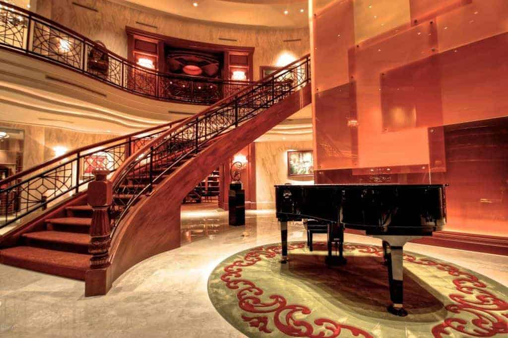 A grand piano sits on the bordered rug in this brown foyer with paneled walls and curved staircase framed with wrought iron railings.