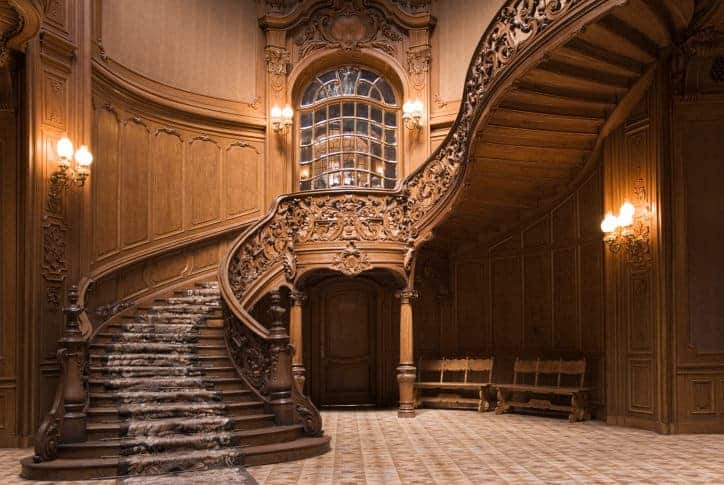 A classic grand foyer featuring classy flooring and elegant carved wooden walls along with decorated staircase with carpeted steps.