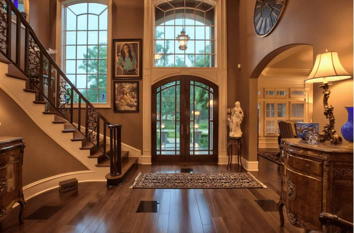 This foyer features brown walls, hardwood floors and a two-story ceiling.