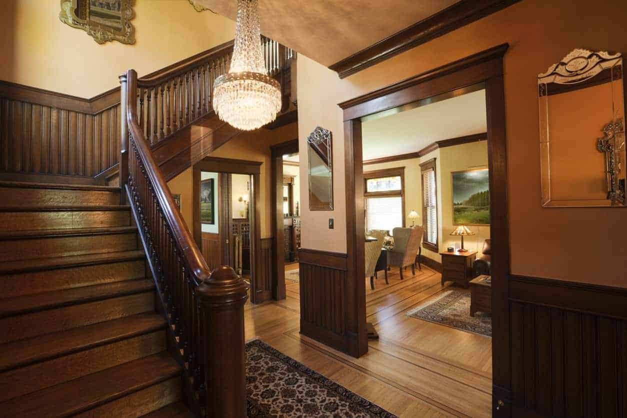 A small brown foyer featuring a wooden staircase, hardwood flooring and fancy ceiling light.