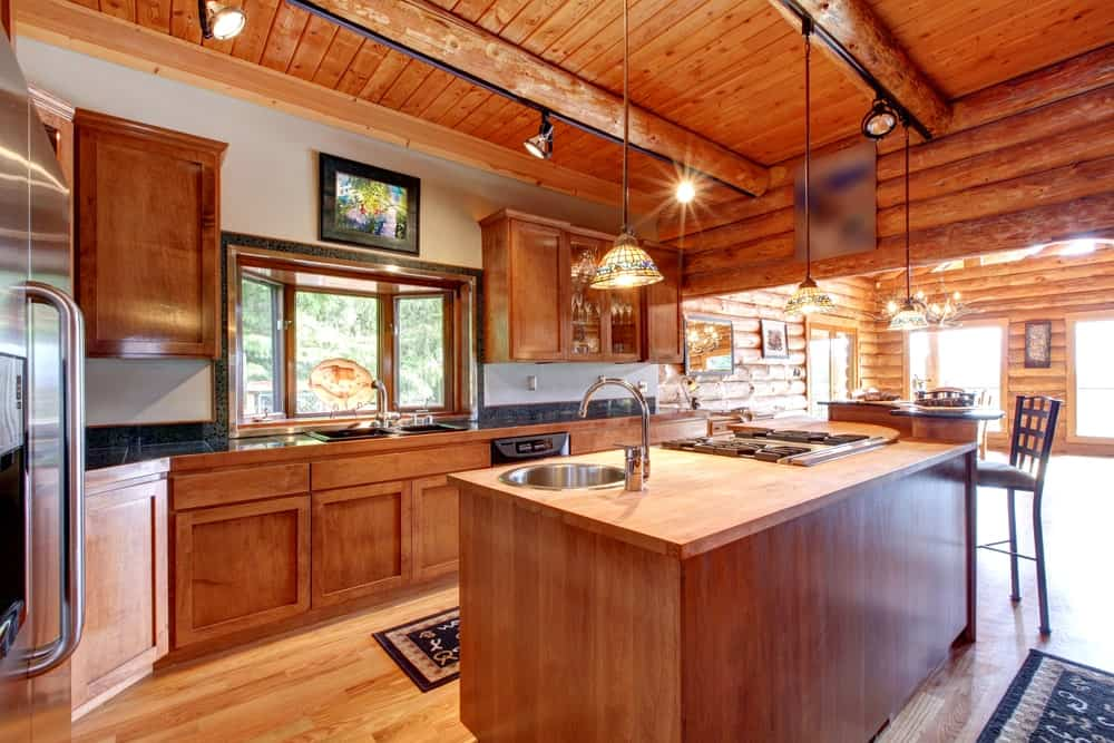 The smooth hardwood flooring contrasts the textured log cabin wooden ceiling with exposed log beams. These log beams support rows of modern spotlights and a trio of pendant lights that shine warm yellow light over the wooden kitchen island that matches with the peninsula.